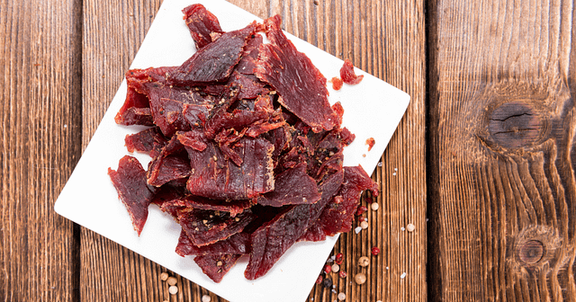 Beef Jerky on a white board on a wood table