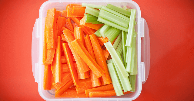 Carrots and Celery in a plastic container on an orange table