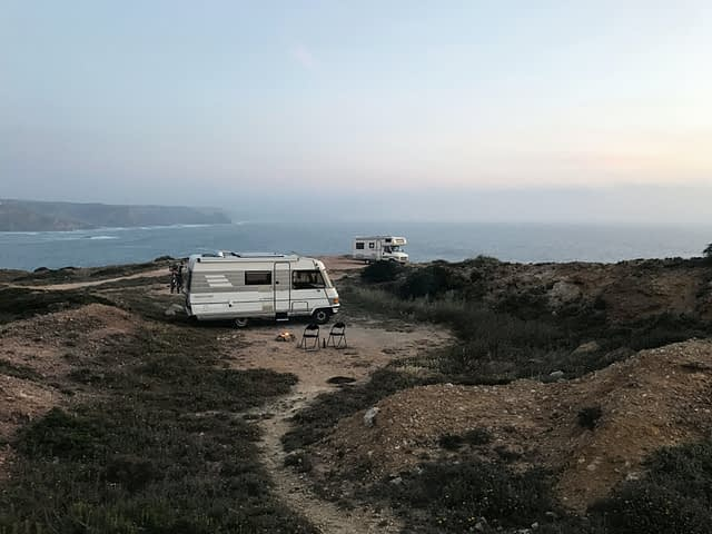 Two RVs camping next to the ocean